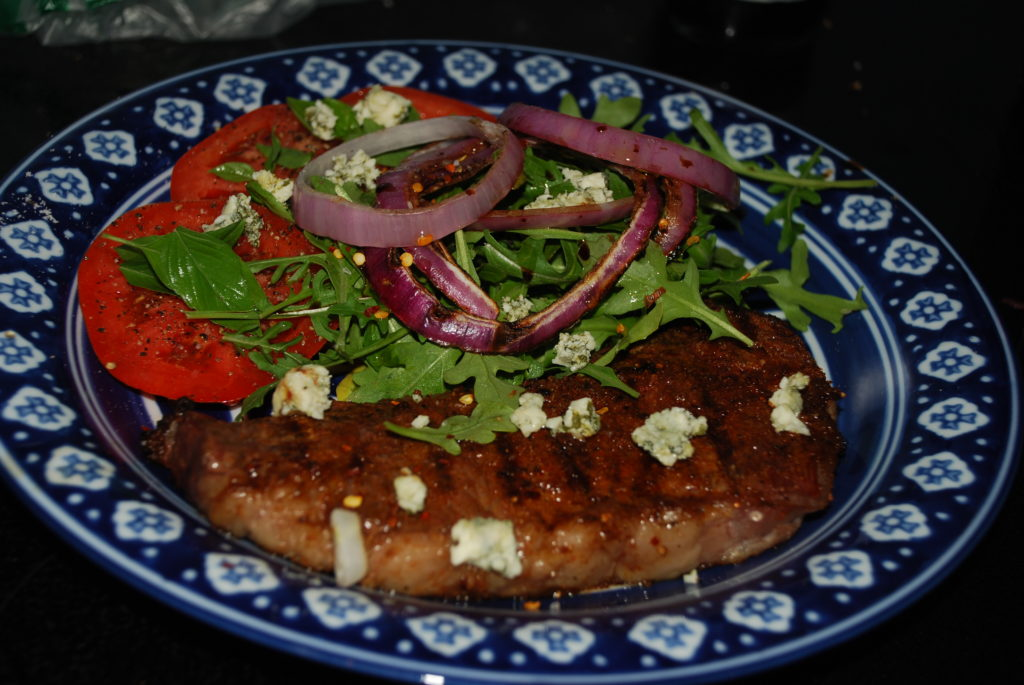 Grilled smoked paprika rubbed New York strip with grilled onions, arugula and gorgonzola.