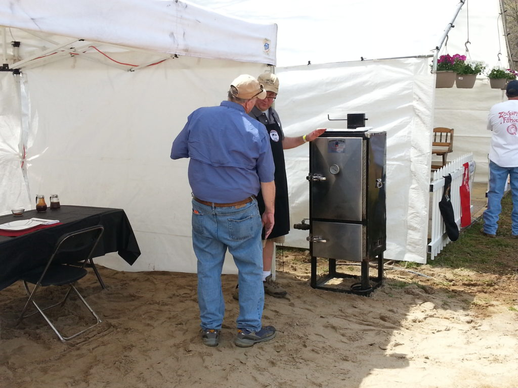Sweet Swine O' Mine's Dr. Richard Lackie presenting on-site ribs to a judge in Atoka, TN.  Inventory: Backwoods Smoker, Pop-up tent, table, chair, and plastic table cloth.  That is IT (mostly).  Notice the team next door has a floor, fence on the front, and plants hanging.  It's nice to have, but we took 1st place in ribs without it.