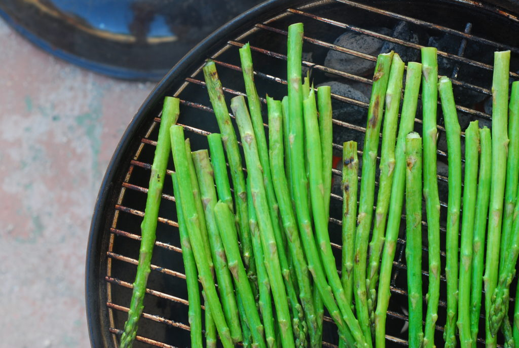 You can grill asparagus directly on the grates without them falling through by keeping them perpendicular or diagonal to the grates.